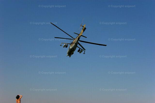 Russischer Militärhubschrauber | Eine Frau schaut nach oben zu einem über sie fliegenden Hubschrauber.