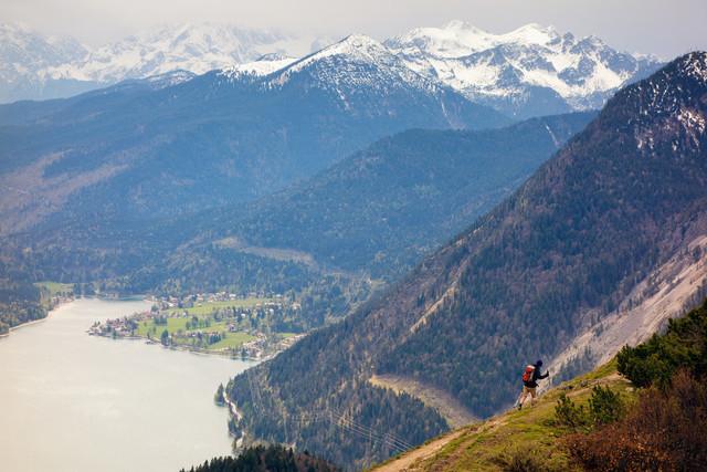 Wanderer am Jochberg mit Blick auf den Walchensee | Blick vom Jochberg ins Tal auf den Walchensee und schneebedeckte Berge