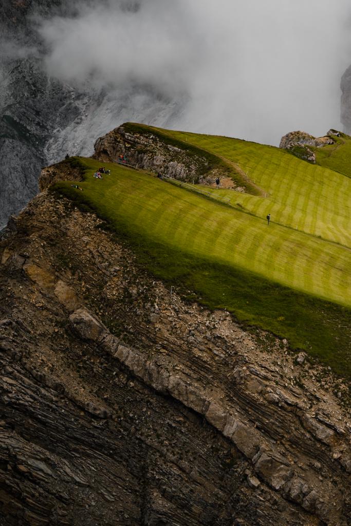 Bitte net stolpern | Auf 2.500 m findet man die Platte der Seceda, das plötzliche Ende einer langsam ansteigenden Alm. Das Bild zeigt eine Gruppe von Wanderern, die sich kurz vor dem Abgrund vom Aufstieg erholen.