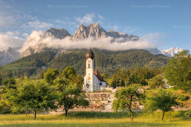Morgenstimmung in Grainau in Bayern   Blick zur Pfarrkirche St. Johannes der Täufer in Obergrainau, vor der mächtigen Kulisse des Wettersteingebirges mit der Alpspitze links hinter den Wolken, dem Großen Waxenstein in der Bildmitte und der Zugspitze rechts im Hintergrund.