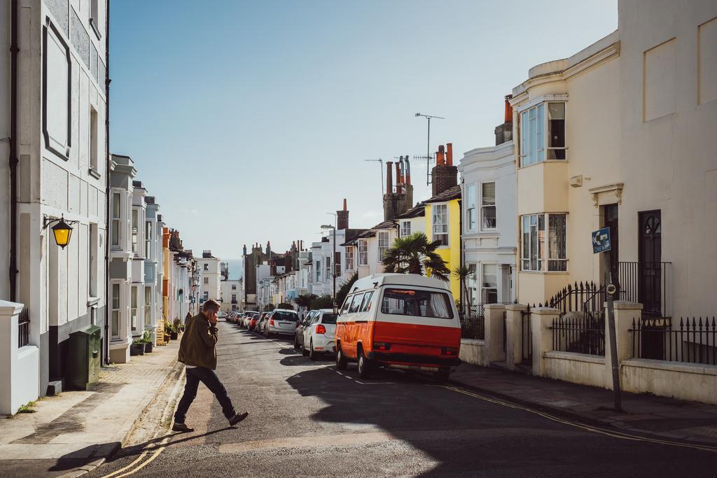 Brighton | Mann überquert Straße beim telefonieren, britische Architektur, Brighton, England