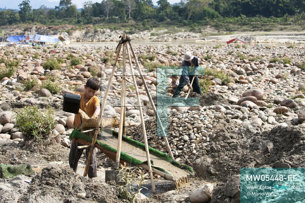 MW05448-FF | Myanmar | Kachin State | Myitson | Adee spült den Flusssand über die Holzrutsche und hofft, dass winzige Goldpartikel in der grünen Matte zurückbleiben. Der 13-jährige Maung Adee lebt mit seiner Tante und seinem Onkel im Dorf Thanphe, drei Kilometer vom Zusammenfluss des Ayeyarwady. Dort schürft Adee mit seiner Familie nach Gold.  ** Feindaten bitte anfragen bei Mario Weigt Photography, info@asia-stories.com **