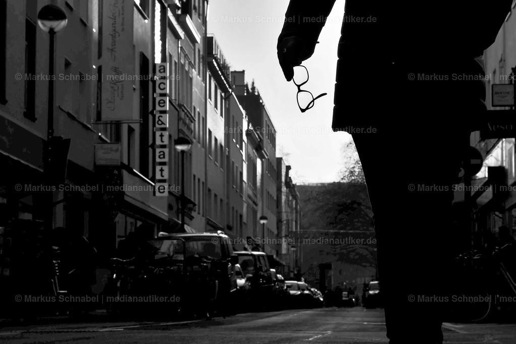 Durch die Brille | Mann mit Brille in der Hand unterwegs auf dem kleinen Plätzchen zwischen Pfeilstraße, Kettengasse und Ehrenstraße.