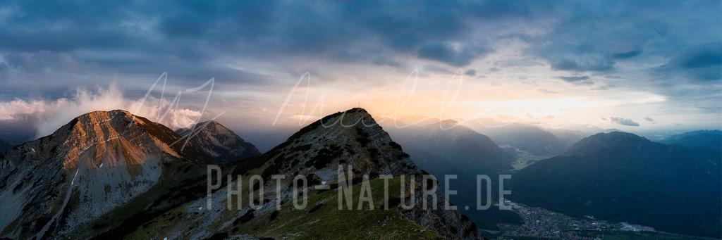 Dramatischer Sonnenuntergang im Estergebirge | Die letzten Sonnenstrahlen durchdringen die Wolkendecke und lassen die Berggipfel in einem weichen Licht erstrahlen