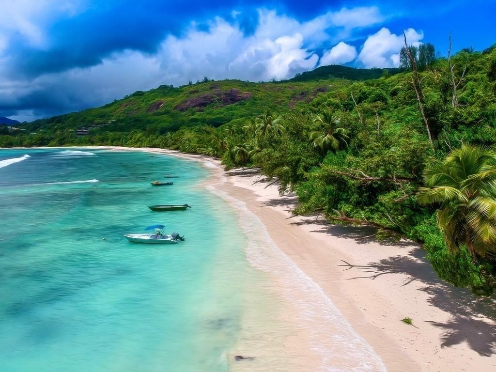 Drohnenaufnahme vom Strand Baie Lazare auf den Seychellen | Türkisblaues Wasser und ein paar Boote am Traumstrand mit einer Luftaufnahme