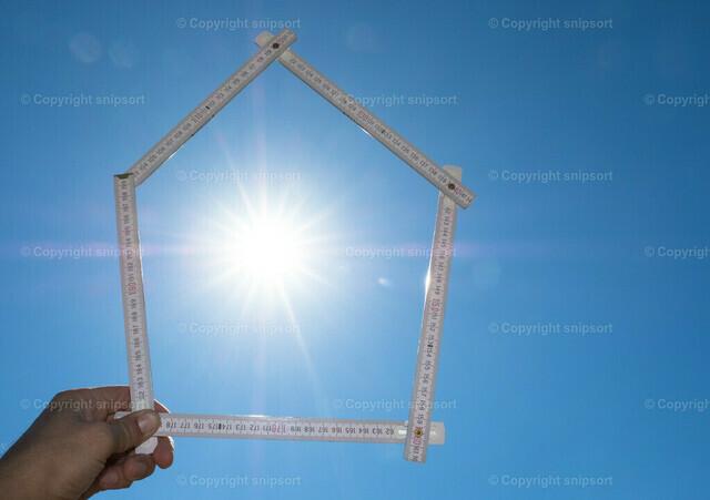 Konzept Freude auf Eigenheim | Eine Hand hält einen zu einem Haus gefalteten Zollstock gegen eine strahlende Sonne.