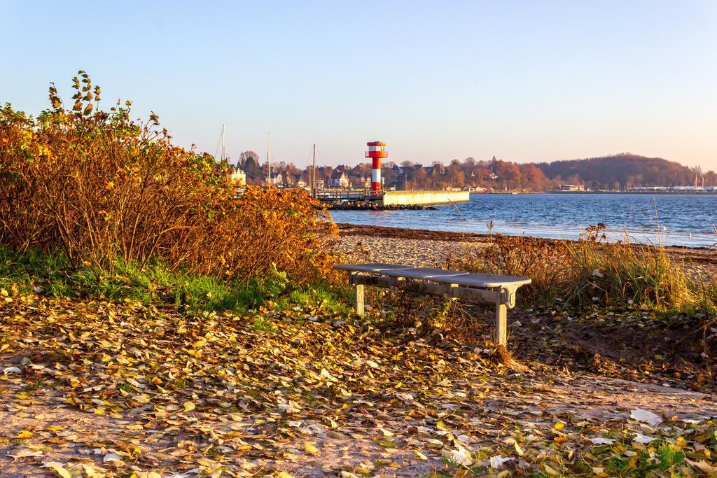 Strand in Eckernförde   Bank am Strand in Eckernförde mit Blick auf den Leuchtturm