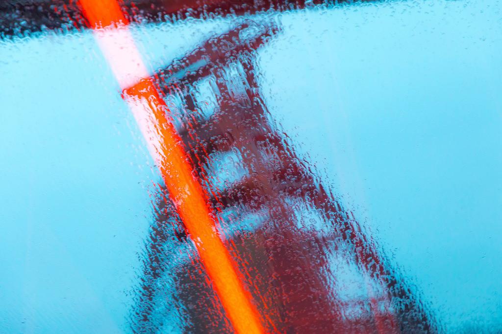 JT-180312-082 | Welterbe Zeche Zollverein, Fördergerüst Schacht 12, Essen, gesehen durch die Regennasse Glasscheibe der Rolltreppe zum Ruhrmuseum, Lichtreflexe der rot beleuchteten Fahrtreppe,