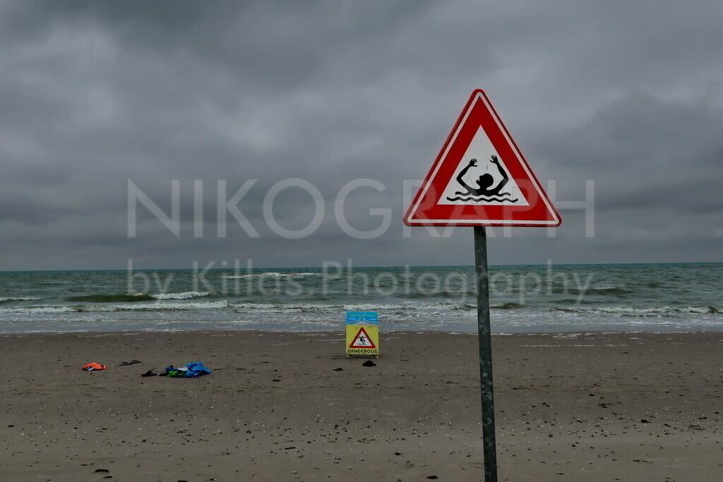 Warnschild am Strand   Ein Warnschild am Strand der Nordseeinsel Texel warnt vor den Gefahren der Strömung.