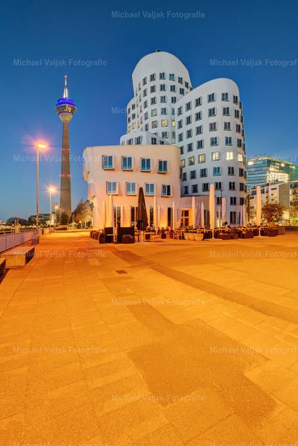 Im Medienhafen Düsseldorf | Blick zu einem der drei Gehrybauten am Neuen Zollhof im Düsseldorfer Medienhafen und dem Rheinturm im Hintergrund. Nach Einbruch der Dämmerung wird der Platz in ein orangenes Licht getaucht.