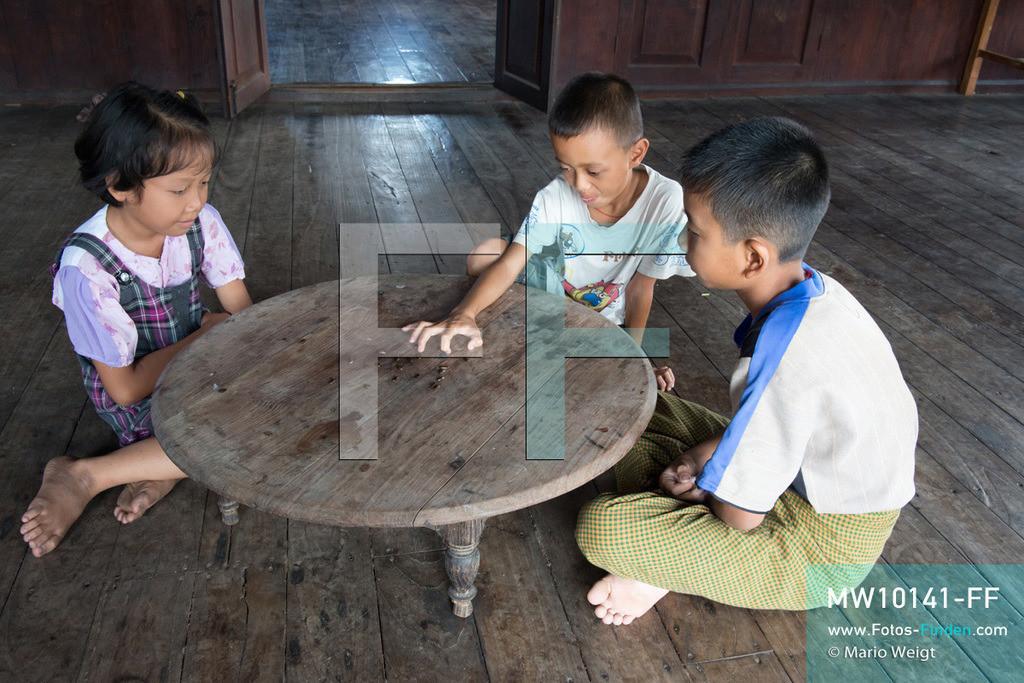 MW10141-FF | Myanmar | Inle-See | Nyaungshwe | Reportage: Ye Lin lebt auf dem Inle-See | Ye Lin spielt mit seiner Schwester Than Dar Aung und seinem Freund eine Art Mini-Billard mit Kürbiskernen. Der 8-jährige Ye Lin Yar Zar lebt mit seinen Eltern in einem Pfahlhaus auf dem Inle-See. Er gehört zur ethnischen Gruppe der Intha und beherrscht die einzigartige Einbeinrudertechnik, um zur Schule zukommen.  ** Feindaten bitte anfragen bei Mario Weigt Photography, info@asia-stories.com **