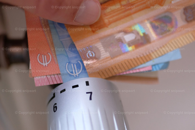 Eine Nebenkostenabrechung mit Geldscheinen und einem Thermostatventil | Konzept für eine Nebenkostenabrechnung mit Thermostatventil am Heizkörper und Geldscheinen.
