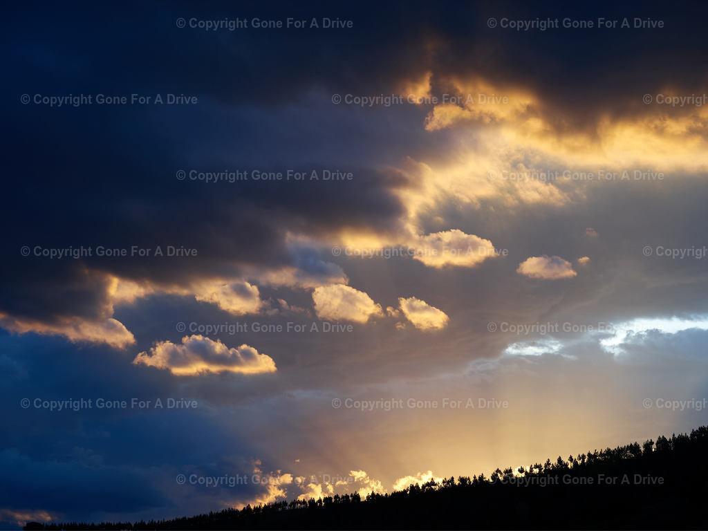 Neuseeland   Gewitterwolken, die von der hinter einer Hügelkuppe untergehenden Sonne angestrahlt werden