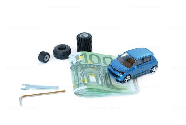 Konzept Kosten Werkstatt | Ein Modellauto auf 100-Euro-Scheinen neben Reifen und Werkzeug