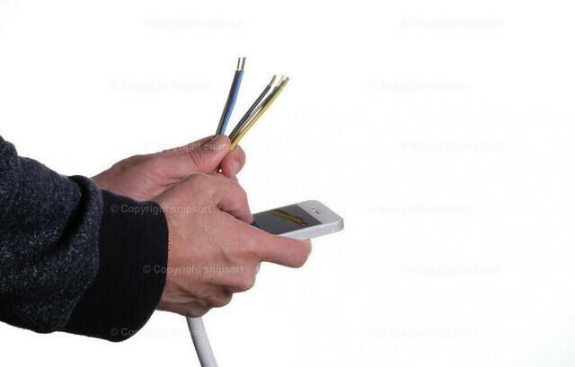 Ein Mann schlägt wegen Stromverdrahtung nach | Konzept von einem Mann, der die Farben für die Stromadern am Smartphone nachschlägt.