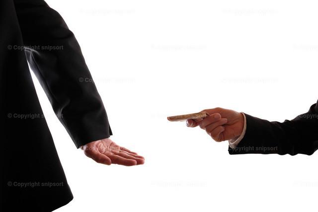 Heimliche Annahme von Bestechungsgeld | Ein mann im Anzug steckt heimlich einem anderen Mann Geld zu.
