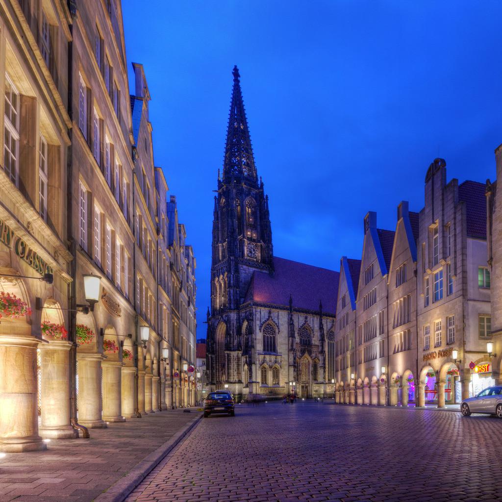 Prinzipalmarkt mit Lambertikirche in Münster bei Nacht   Mit Blumen geschmückter Prinzipalmarkt und Lambertikirche bei Dämmerung in Münster Westfalen mit buntem Kopfsteinpflaster in der blauen Stunde