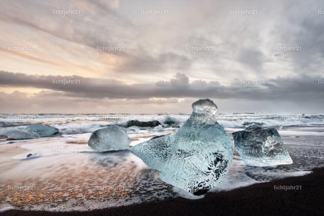 Eisblöcke am schwarzen Strand   Eisblöcke in blauen und dunklen Farbtönen an einem schwarzen Strand mit starker Brandung, das Eis spiegelt sich im nassen Sand, im Hintergrund rollen Wellen heran, Himmel mit farbigem Abendlicht - Location: Island, Jökulsarlon (Jökulsárlón)