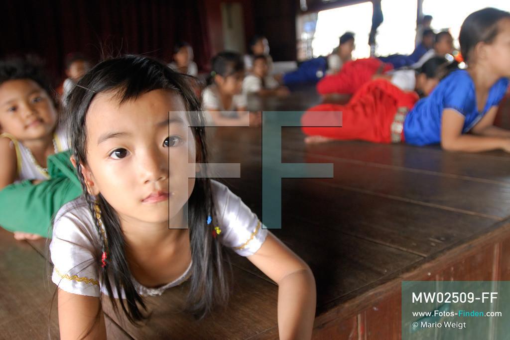 MW02509-FF | Kambodscha | Phnom Penh | Reportage: Apsara-Tanz | Tanzschülerinnen lernen den Apsara-Tanz in einer Tanzschule. Sechs Jahre dauert es mindestens, bis der klassische Apsara-Tanz perfekt beherrscht wird. Kambodschas wichtigstes Kulturgut ist der Apsara-Tanz. Im 12. Jahrhundert gerieten schon die Gottkönige beim Tanz der Himmelsnymphen ins Schwärmen. In zahlreichen Steinreliefs wurden die Apsara-Tänzerinnen in der Tempelanlage Angkor Wat verewigt.   ** Feindaten bitte anfragen bei Mario Weigt Photography, info@asia-stories.com **