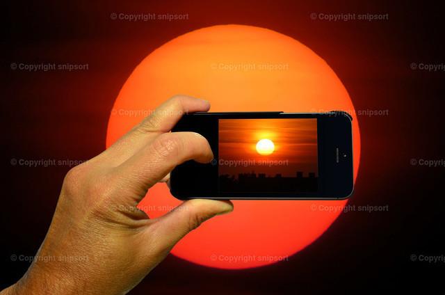 Männliche Hand fotografiert Sonne mit dem Smartphone