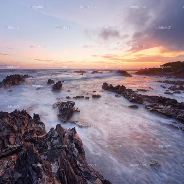 Wilde Küste im Abendlicht | Einsamer Felsenstrand mit Brandung kurz nach Sonnenuntergang, Rot- und Gelbtöne am Himmel, Wasserbewegung in Langzeitbelichtung, Tiefenwirkung - Location: Portugal, Azoren, Insel Corvo