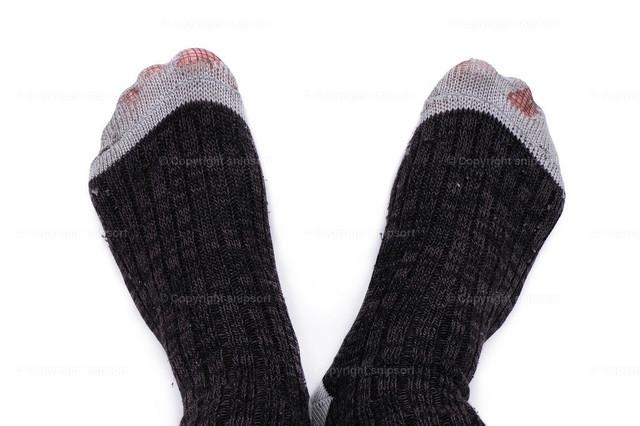 Zerrissene Socken | Löchrige Socken als Konzept für Armut (isoliert über weißem Hintergrund)