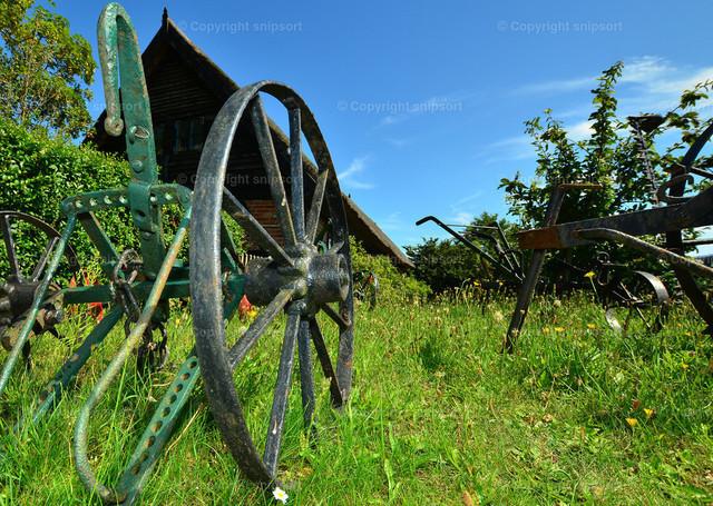 Alter Pflug | Alter, historischer Pflug mit einem Bauernhaus im Hintzergrund