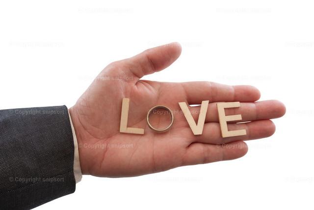 Hand mit Ring und Holzbuchstaben, die das Wort