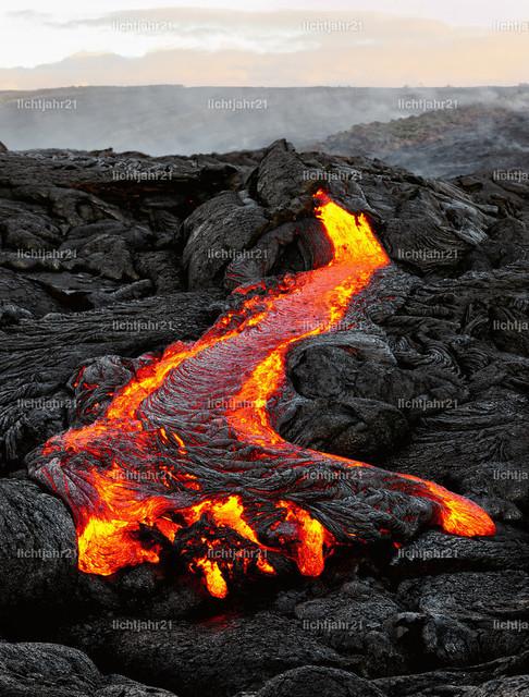 Hawaii - Lava tritt aus einer Erdspalte aus | Ein Lavastrom tritt aus einer Erdspalte aus und fließt in einer schwarzen Vulkanlandschaft, die glühende Lava kühlt langsam ab und erstarrt, am Himmel zeigt sich das erste Tageslicht - Location: Hawaii, Big Island, Vulkan Kilauea