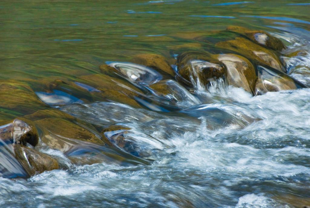 Best. Nr. wasser04   Kiesel im Wasser eines tropischen Flusses, Hawai'i, USA   Das Element Wasser steht mit dem Norden in Verbindung, seine Farben sind blau, blauviolett und schwarz, seine Form ist wellig oder tropfenförmig oder unregelmäßig. Wasser passt sich jeder Form an und formt doch diedie Umgebung. Es steht in Verbindung mit Kommunikation, Übermittlung von Ideen und den Künsten, daher eignen sich die Motive besonders für Kreativagenturen und das Umfeld der (digitalen) Medien, zu Hause sind das Badezimmer aber auch das Arbeitszimmer typische Orte, an denen Wasserbilder eingesetzt werden können.