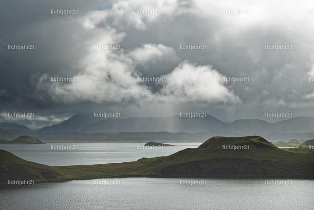 Island - Sonne und Regen am See Myvatn | Großer See mit Inseln, eingerahmt von Bergen, einzelne Bereiche sind von der Sonne beleuchtet, im Hintergrund graue Wolken und Regenschleier - Location: Island, See 'Myvatn'