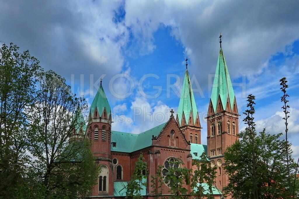 St. Aloysius Iserlohn   Die römisch-katholische Pfarrkirche St. Aloysius in Iserlohn im Sonnenlicht. Die imposanten Kirchtürme ragen den Wolkenhimmel entgegen.