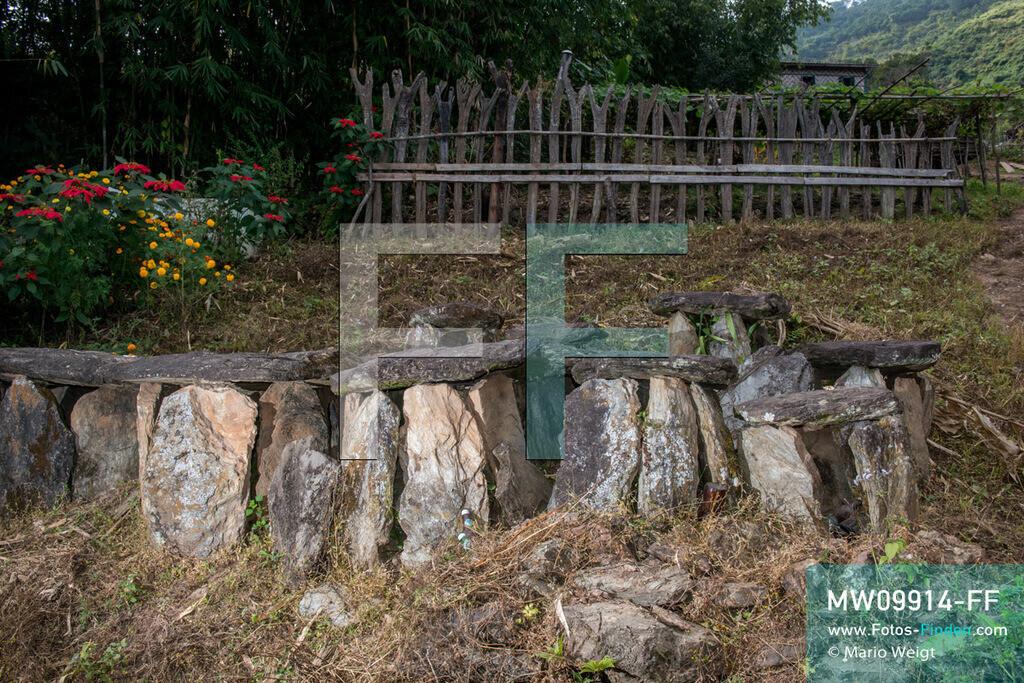 MW09914-FF | Myanmar | Mindat | Reportage: Mindat im Chin State | Gräber der Volksgruppe der Chin im Bergdorf Loute Pe. Steinplatten werden in einem Kreis aufgestellt, eine dient als Abschluss. Mittig in der Erde befindet sich die Urne. Im Hintergrund: Y-förmige Holzpfähle (Totem) symbolisieren die Anzahl der geopferten Tiere, meist Mithun (Wildochse) oder Büffel, während eines schamanischen Rituals oder einer großen Feierlichkeit. Demnach zeigen die Pfosten auch den Reichtum der Chin-Familie.   ** Feindaten bitte anfragen bei Mario Weigt Photography, info@asia-stories.com **