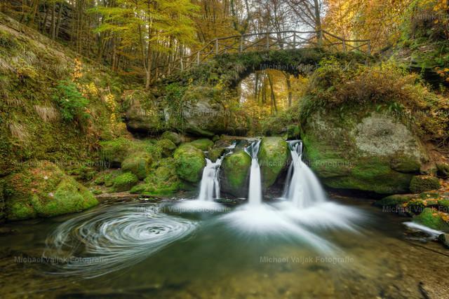 Schiessentümpel in Luxemburg #1  | Herbstliche Aufnahme des kleinen malerischen Schiessentümpel-Wasserfalls in der Region Müllerthal in Luxemburg. Das Wasser der Schwarzen Ernz schießt in drei Strömen über eine Felskante in ein darunter liegendes Wasserbecken und verläuft dann in Richtung der Ortschaft Müllerthal weiter. Er ist zusammen mit der idyllischen Brücke aus Stein und Holz, den umliegenden Felsen und der üppigen Vegetation zu einem der beliebtesten Ausflugsziele in der Region Müllerthal geworden (auch Kleine Luxemburger Schweiz genannt).