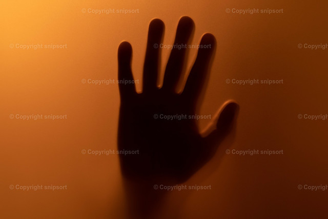 Handsilihouette hinter rötlich schmimmerndem Milchglas | Ein gruselhaft wirkender Handschatten hinter einer blutrot beleuchteten Milchglasscheibe.