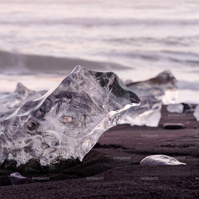 Eisblöcke im Abendlicht | Markante Eisformationen an einem schwarzen Lavasandstrand werden vom Abendlicht mit roten Farbtönen in Szene gesetzt, schmale Schärfenzone, Tiefenwirkung, im Hintergrund die Wellen der Brandung - Location: Island, Südküste, Gletscherlagune Jökulsarlon (Jökulsárlón)