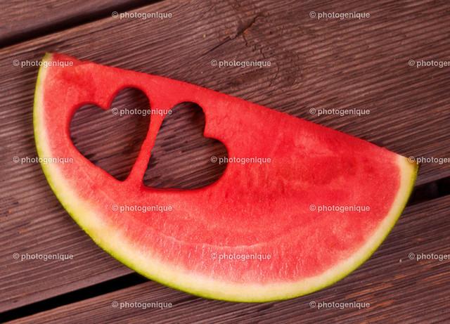 Melone mit zwei Herzen | eine Scheibe Melone auf Holz mit zwei Herz-förmigen Ausschnitten