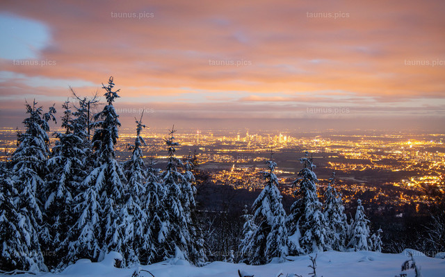 Winter im Taunus | 09.01.2021, Kronberg (Hessen): Blick vom verschneiten Altkönig im Taunus auf das abendliche Frankfurt am Main mit der Skyline.