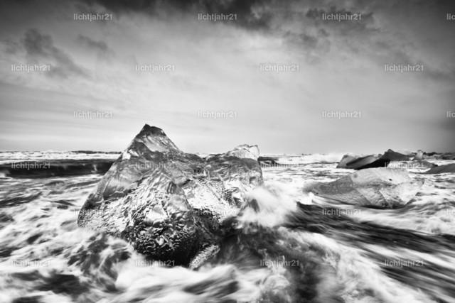 Eisblock in starker Brandung | Schwarzweißbild eines markanten Eisblocks an einem schwarzen Strand mit starker Brandung, Bewegungsspuren des Wassers auf dem dunklen Sand, im Hintergrund weitere Eisblöcke, Wellen rollen heran, kontrastreicher Himmel - Location: Island, Jökulsarlon (Jökulsárlón)