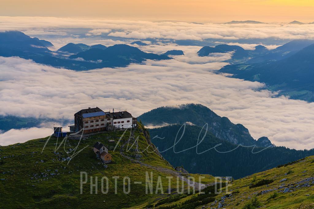 Eine prächtige Lage über den Wolken   Das Watzmannhaus steht in bester Lage in den Berchtesgadener Alpen. Hier wird die Hütte von der Morgensonne in ein warmes Licht gerückt.