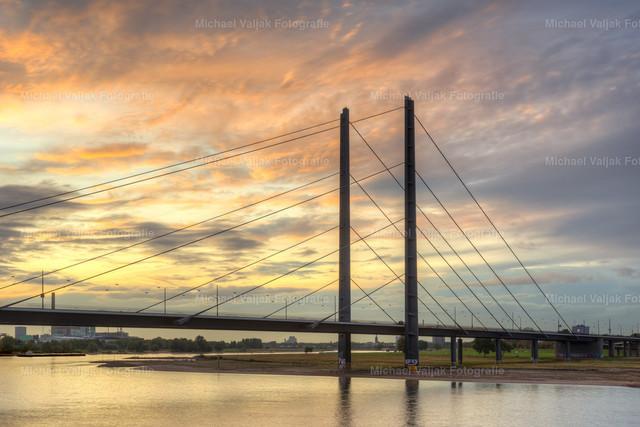 Rheinkniebrücke in Düsseldorf | Blick von der Rheinpromenade in Düsseldorf zur Rheinkniebrücke bei einem bunten Sonnenuntergang im Herbst.