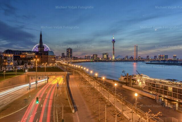 Düsseldorf Rheinufertunnel und Skyline | Blick von der Oberkasseler Brücke zur Einfahrt in den Rheinufertunnel, der entlang der Rheinpromenade in Richtung Medienhafen führt. Hinter der Kirche Sankt Lambertus steht auf dem Burgplatz das Riesenrad