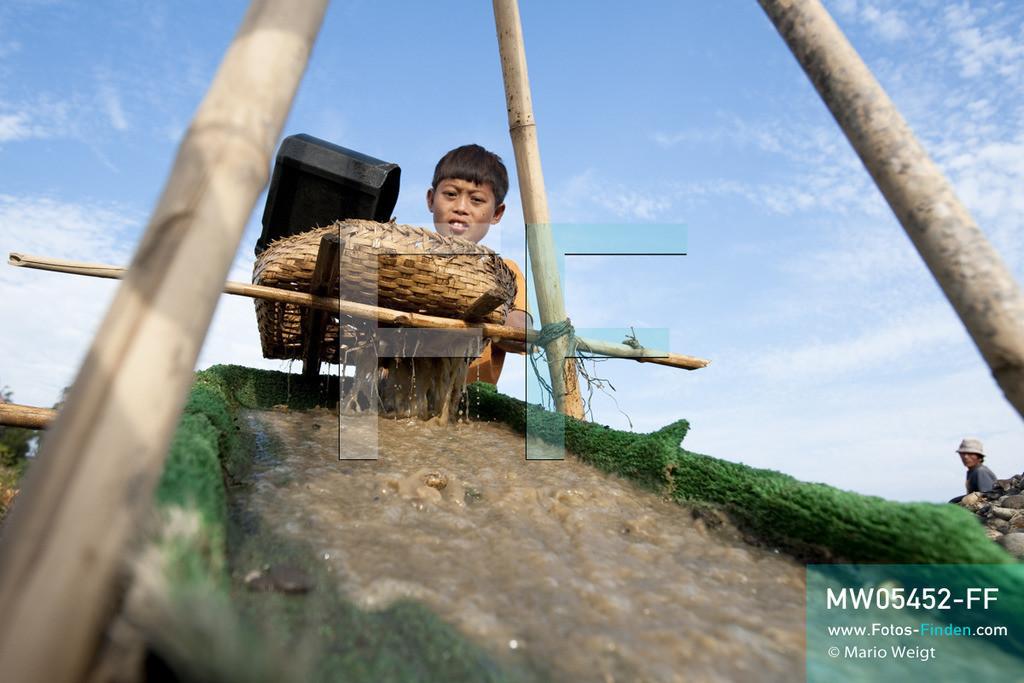 MW05452-FF   Myanmar   Kachin State   Myitson   Adee spült den Flusssand über die Holzrutsche und hofft, dass winzige Goldpartikel in der grünen Matte zurückbleiben. Der 13-jährige Maung Adee lebt mit seiner Tante und seinem Onkel im Dorf Thanphe, drei Kilometer vom Zusammenfluss des Ayeyarwady. Dort schürft Adee mit seiner Familie nach Gold.  ** Feindaten bitte anfragen bei Mario Weigt Photography, info@asia-stories.com **
