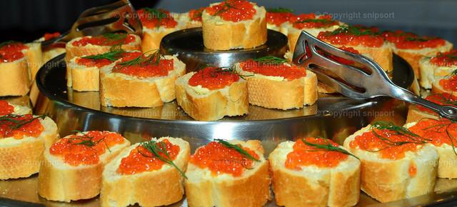 Brot mit Kaviar | In Scheiben geschnittene Baguetts mit rotem Kaviar drauf.