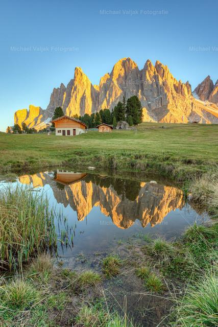 Bei der Geisleralm im Villnösstal in Südtirol | Blick von den Wiesen bei der Geisleralm zu den Geislerspitzen, die sich in einem kleinen Teich spiegeln.
