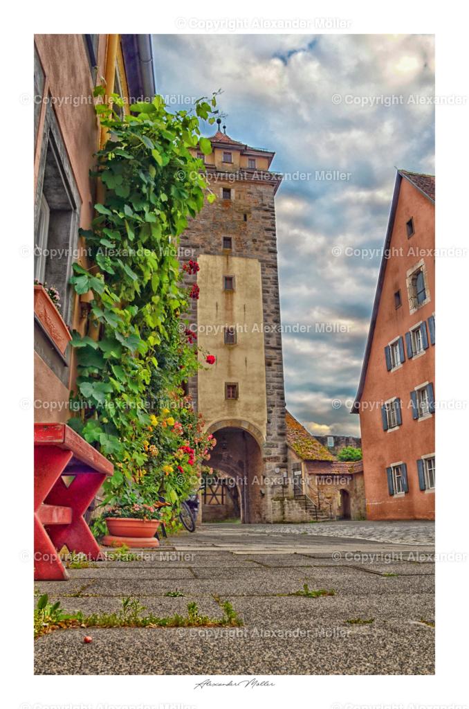 """Rothenburg ob der Tauber No.64    Dieses Werk zeigt Das Spitaltor. Die dahinter liegende Spitalbastei war eine der Wehranlagen der Stadt Rothenburg und diente der Abschreckung. Erreicht wurde dies durch eine übertrieben bullige Bauweise und ein System mit mehreren Toren. Diese massive Wehr stammt aus dem 17. Jahrhundert und ist damit die jüngste Anlage des Ortes ihrer Art. """"Pax intrantibus, salus exeuntibus"""", zu Deutsch """"Friede den Eintretenden, Heil den Hinausgehenden"""", so begrüßt das mächtige Bollwerk seine Besucher. In Form einer Acht hatte Leonhard Weidmann Ende des 16. Jahrhunderts die beeindruckende Wehranlage geschaffen. Sieben Tore, ein Fallgitter, eine Zugbrücke und ein von Geschützen befahrbarer Wallgang schützten Rothenburg vor Angriffen aus dem Süden. Das Zeugnis Rothenburger Verteidigung lässt sich auch innerhalb der Mauern auf dem Wallgang erkunden."""