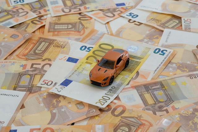 Orangenfarbenes Auto auf unzähligen Geldscheinen | Ein Modellauto auf flächendeckend ausgelegten 50-Euro-Banknoten mit 200-Euro-Banknote zum Thema Konzept Autokosten