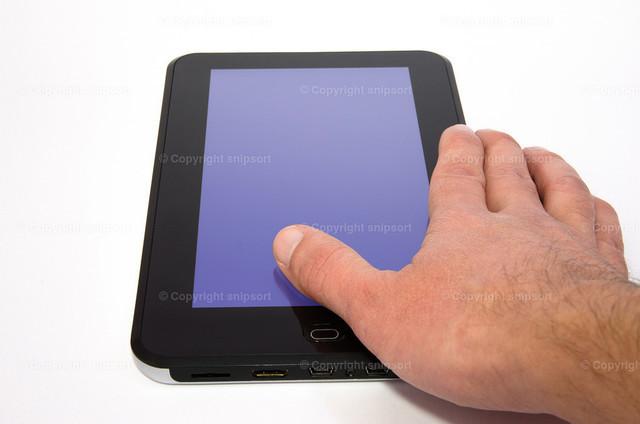Tablet | Rechte männliche Hand liegt auf einem Tablet.