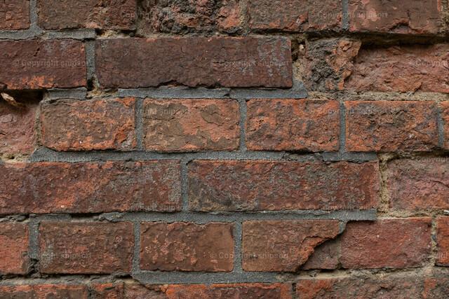 Backsteinwand | Eine alte, abgeblätterte Wand aus roten Backsteinen.