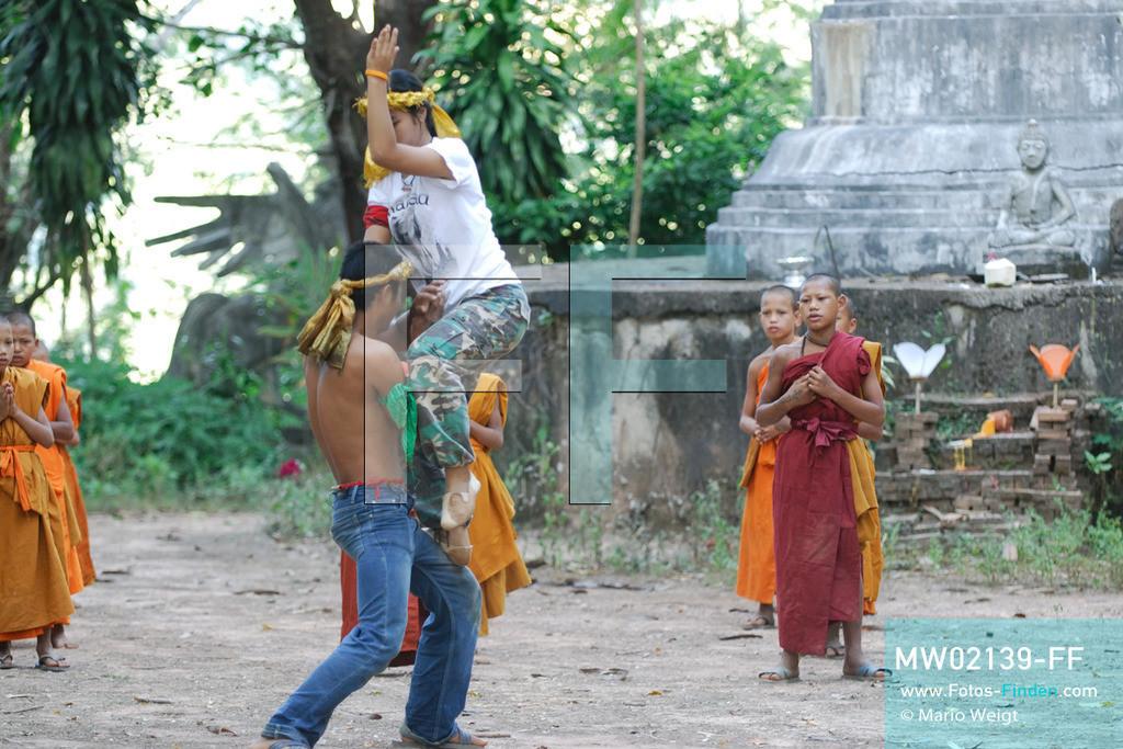 MW02139-FF | Thailand | Goldenes Dreieck | Reportage: Buddhas Ranch im Dschungel | Abt Phra Khru Bah Nuachai Kosito, sein Sohn Decho und seine  Tochter Nopphakao lernen den jungen Mönchen Muay Thai (Thaiboxen). Novize Pansaen in der roten Robe schaut konzentriert zu.  ** Feindaten bitte anfragen bei Mario Weigt Photography, info@asia-stories.com **